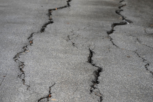 Макрофотография фото трещины асфальт на местной дороге или улице после землетрясения или эль-ниньо.