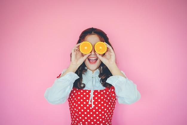 ピンクの背景に彼女の目の前にオレンジを持つ若い女性の肖像画