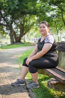 朝の自然公園でアジアの太った女性がリラックスした運動