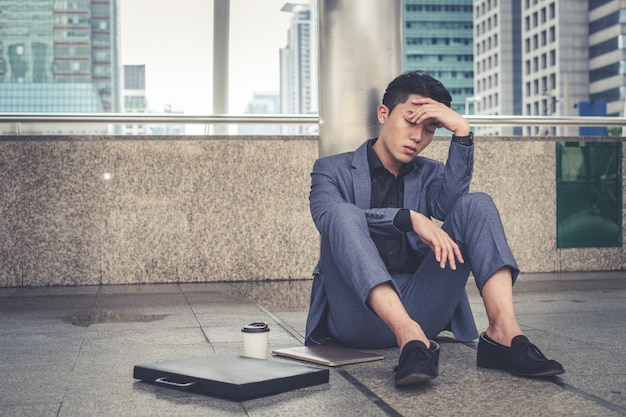 Подавленный и уставший бизнесмен, сидящий в городе