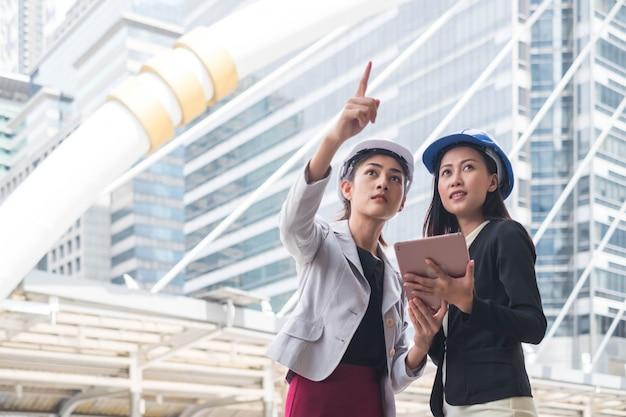 アジアの女性エンジニアと女性ビジネス建設マネージャーフォアマンは、サイトの構築に取り組んでいます。
