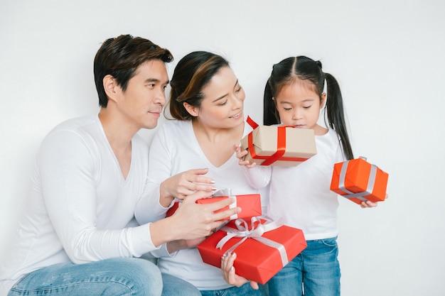 幸せな家族の母、父、子娘自宅でギフトボックスクリスマス、新年あけましておめでとうございますパーティーコンセプト