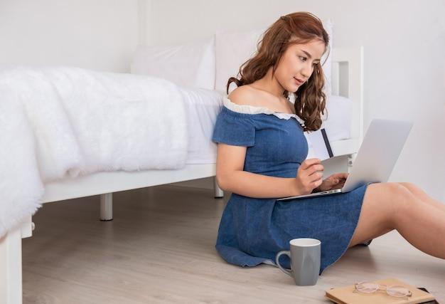 Работа на дому, красивая молодая азиатская женщина работая на портативном компьютере пока сидящ на живущей комнате