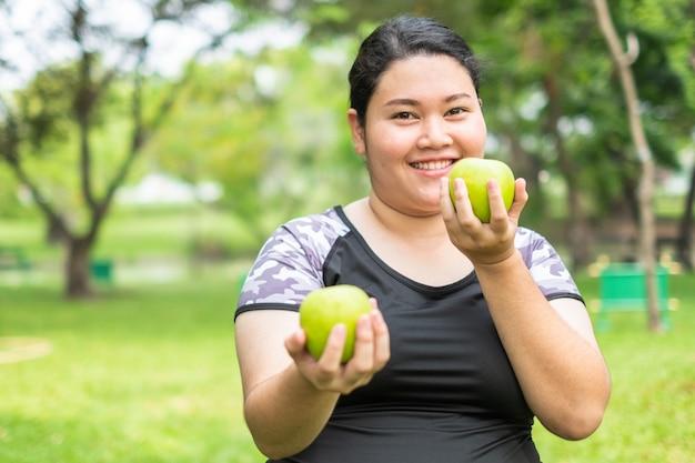 自然公園で青リンゴを保持している若いアジアの脂肪女性