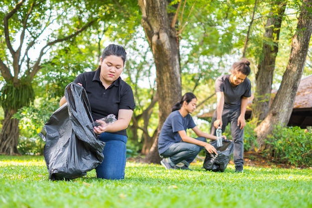Волонтеры молодой женщины выбирая вверх по погани в парке. концепция охраны окружающей среды