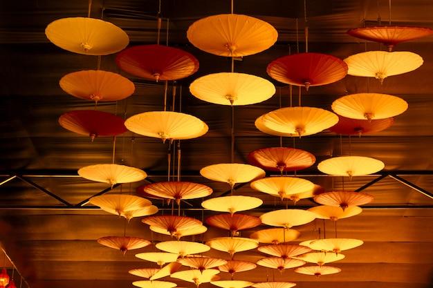 Разноцветный зонт ручной работы висит на потолке