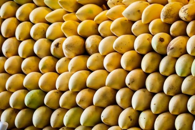 屋台の食べ物や新鮮な果物に沿って巨大なマンゴーの背景