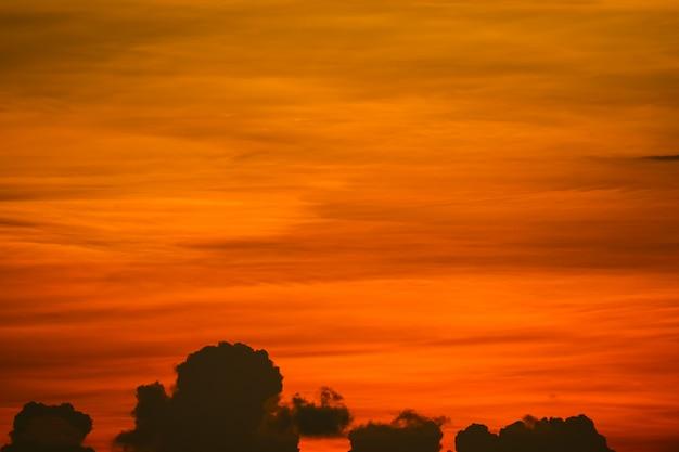 カラフルな夕焼けのオレンジ色の雲と太陽が空に