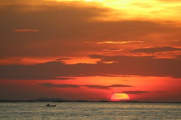 地平線の海の上の夕方の雲に戻る赤黄色の空に沈む夕日