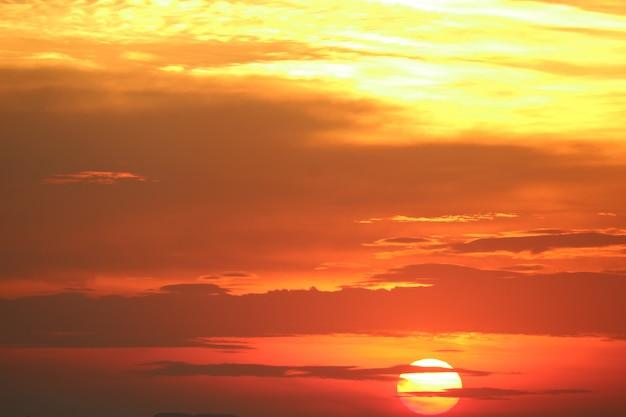 地平線の海の上の赤いオレンジ色の空バックソフト夕方の雲に沈む夕日