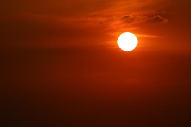 暗い赤オレンジ色の空に沈む夕日