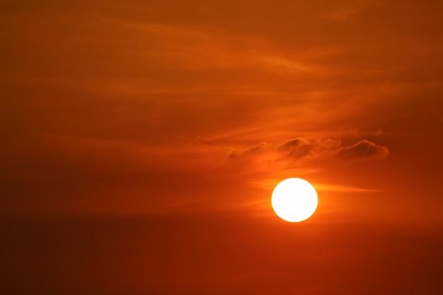暗い赤オレンジ色の空に沈む夕日は柔らかい夕方の雲