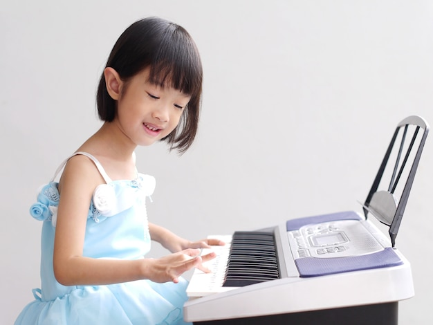 Азиатская девушка играет на пианино