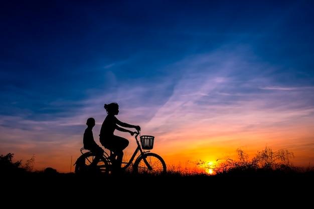 日没の背景でサイクリングするママと子供のシルエット。