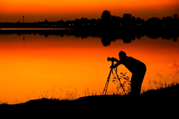 写真家のシルエットは、夕日の背景にある湖で写真を撮っています。