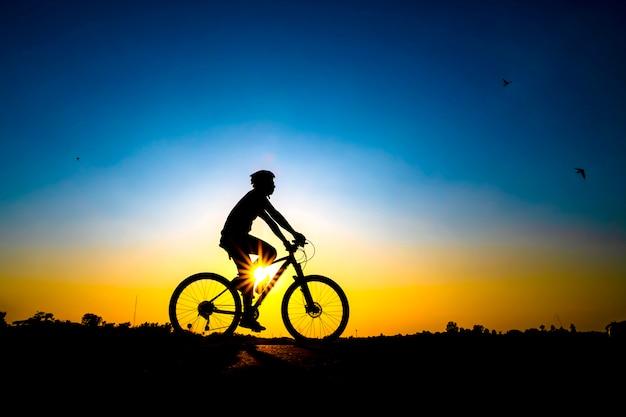Силуэт велосипедиста в фоне заката.