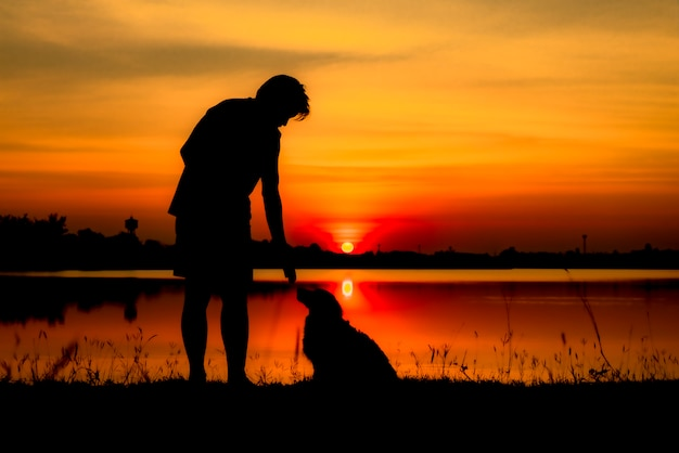 男と夕日を背景に犬のシルエット。