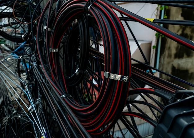 Запутанные электрические провода на городской электрический столб. неорганизованная и грязная для организации концепция управления. крупным планом запутались электрические провода.