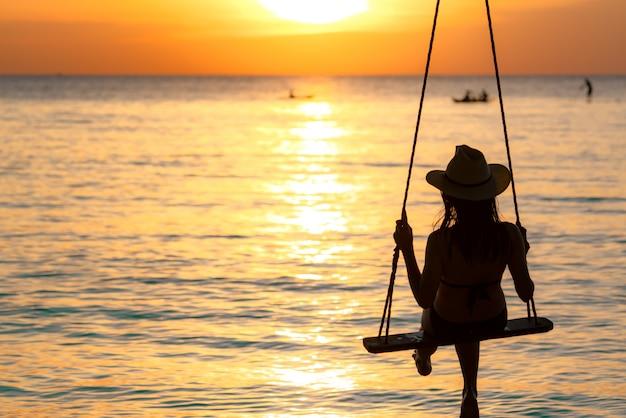 シルエットの女性はビキニを着、麦わら帽子は夕暮れ時の夏休みにビーチでブランコを振る