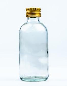 Пустая прозрачная круглая стеклянная бутылка с закрытой алюминиево-желтой крышкой с пустой этикеткой и копией пространства