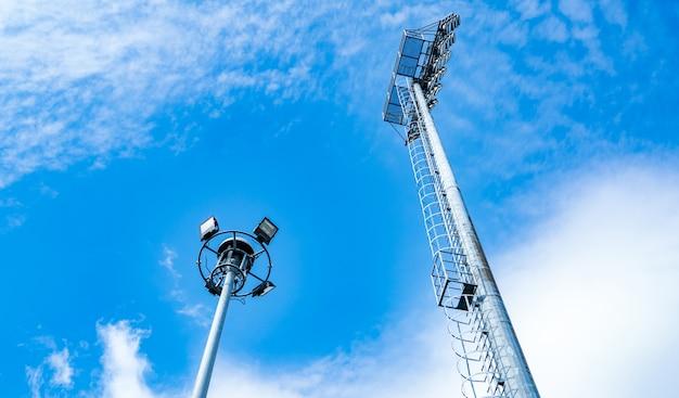 美しい青い空と白い雲のスタジアムのスポーツライト。コピースペース