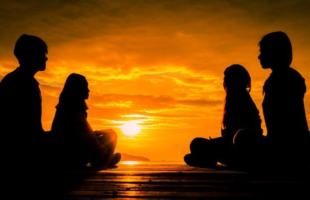Четверо молодых людей сидят на деревянном пирсе на рассвете на пляже, чтобы сделать медитацию с оранжевыми красивыми небом и облаками.