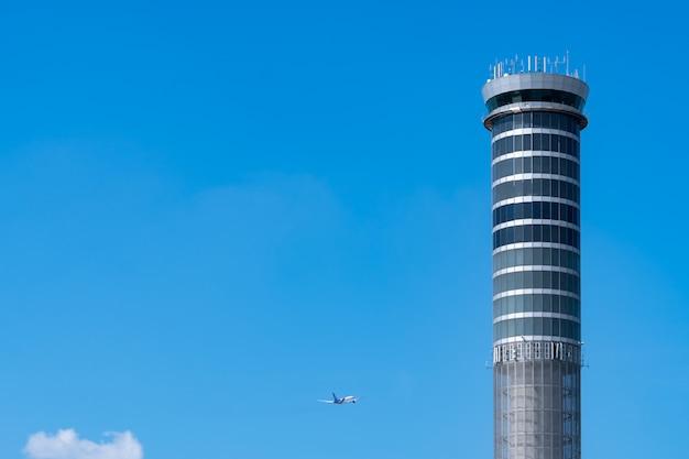 澄んだ青い空に国際飛行飛行機が飛んでいる空港の管制塔。レーダーによって空域を制御するための空港交通管制塔。航空技術。フライト管理。