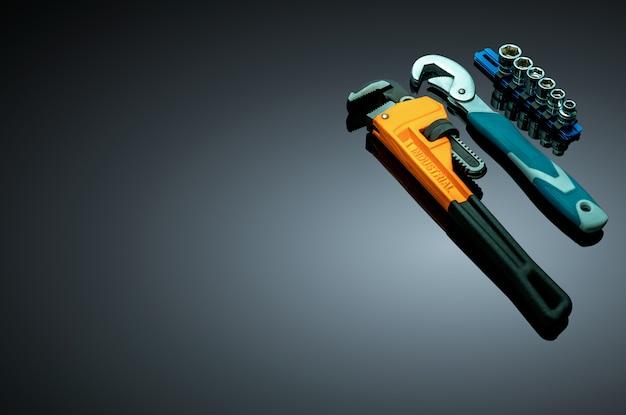 配管工、六角ソケット、暗い背景に分離された曲がったレンチの金属モンキーレンチのセット。メカニックツール。修正および保守サービス用のハードウェア。黒いハンドルが付いている新しいクロムパイプレンチ。