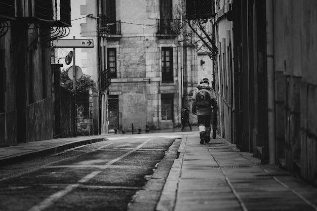 Работник очистить общественный бетонный пол с помощью пылесоса. рабочие используют воздуходувки чистого тротуара в городе. дворник пускает пыль на тротуаре. старая архитектура в европе. узкая аллея и здание.