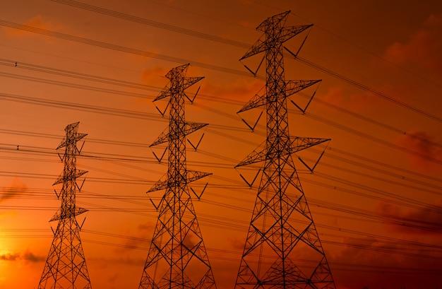 高電圧電気パイロンと夕焼け空と電線。電柱。力とエネルギーの概念。ワイヤーケーブルが付いている高圧グリッドタワー。美しい赤オレンジ色の夕焼け空。インフラ。