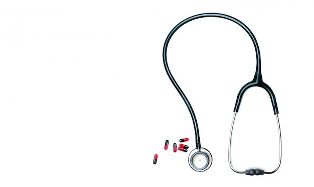 Стетоскоп и красно-черные капсулы таблетки на столе врача или медсестры. проверка здоровья. медицинское здравоохранение и медицина. инструмент врача для диагностики пациента. оборудование врача кардиологии.