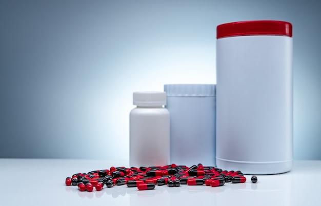 抗生物質のカプセル錠剤は白いテーブルとプラスチックボトルの白い空白のラベルに広がる