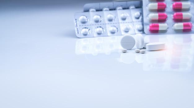 ブリスターパックの白い錠剤の丸薬と白ピンクのカプセルと丸い錠剤