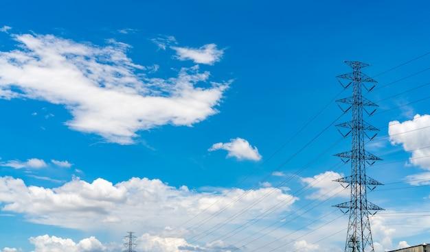 高電圧電気パイロンと青い空を背景の電線