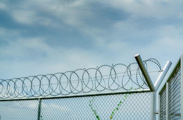 刑務所のセキュリティフェンス。有刺鉄線のセキュリティフェンス。かみそりワイヤー刑務所フェンス。