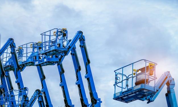青い空を背景に関節式ブームリフト。