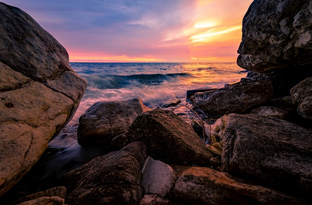 Выплеск воды океана на пляже утеса с розовым и золотым небом захода солнца. волна моря брызгая на береге камня на море на лете. мягкая волна