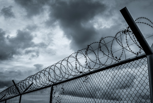 刑務所のセキュリティフェンス。有刺鉄線のセキュリティフェンス。バリア境界。境界セキュリティ壁。プライベートエリア。ミリタリーゾーンのコンセプトです。