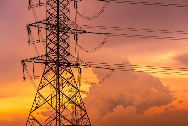 高電圧電気パイロンと夕焼け空と電線。電柱。力とエネルギーの概念。ワイヤーケーブルが付いている高圧グリッドタワー。