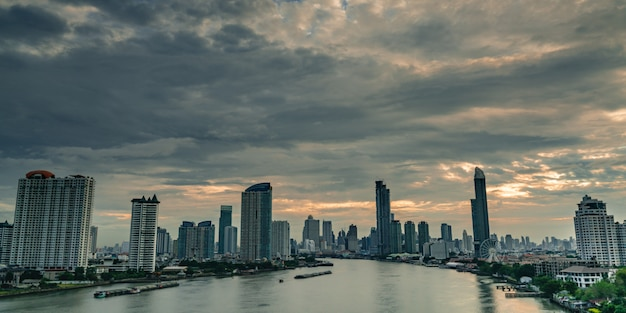 オレンジ色の日の出の空とタイのバンコクで雲と朝の川の近くのモダンな建物の街並み。朝の空と観覧車と高層ビル。