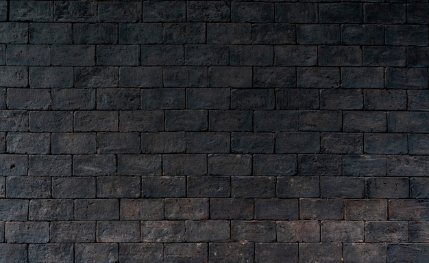黒と茶色のレンガの壁の大まかなテクスチャ背景。感情的な悲しみのための暗いレンガの壁。エクステリアアーキテクチャ。