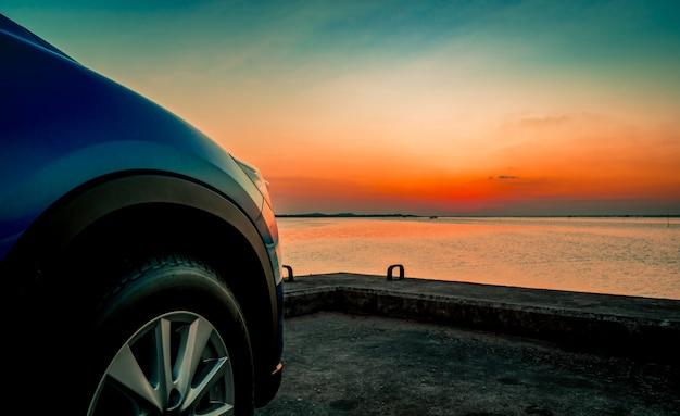 Синий компактный внедорожник со спортивным и современным дизайном припаркован на бетонной дороге у моря на закате.