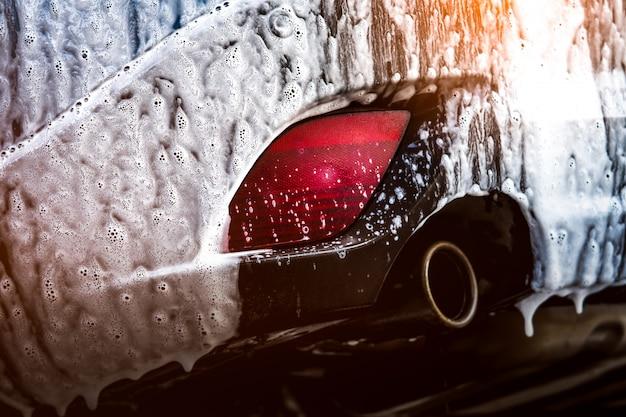 Синий компактный внедорожник со спортивным и современным дизайном, мойка с мылом. автомобиль покрыт белой пеной. автосервис бизнес-концепция. автомойка с пеной перед воском и автомобильным покрытием