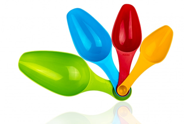 影で白い背景に分離されたカラフルなプラスチック計量スプーンのセット。緑、青、赤、オレンジのプラスチック製計量スプーン。