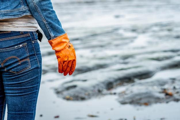 ボランティアはジーンズと長袖のシャツを着て、オレンジ色のゴム手袋を着用してビーチでゴミを収集します。ビーチ環境。ビーチを掃除する女性。ビーチでゴミを片付けます。