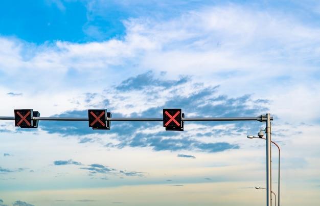 青い空と白い雲の背景にサインの十字の赤い色の信号機。間違ったサイン。進入禁止の標識。赤十字案内は、信号機の信号を停止します。警告信号。