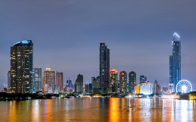 夜の川の近くのモダンな建物の街並み。近代建築のオフィスビル。夕方の空と高層ビル。黒と白のトーン画像。川沿いの建物の夜の写真。
