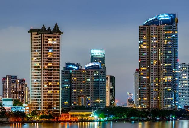 夜の川の近くのモダンな建物の街並み。近代建築のオフィスビル。夕方の空と高層ビル。川沿いの建物の夜の写真。夜のマンションオープンライト。