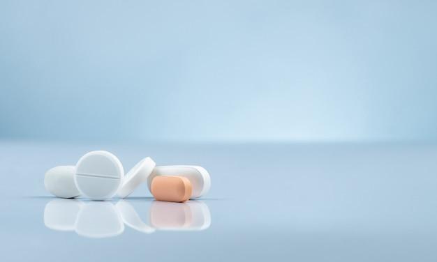 薬局ドラッグストア製品。グラデーションの背景にオレンジと白の錠剤の山。異なるサイズと形状の錠剤の丸薬。製薬産業。病院の薬。小売医薬品市場。