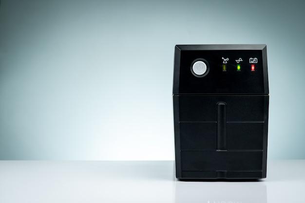 Бесперебойный источник питания. ибп резервного питания с аккумулятором, изолированные на столе. ибп для пк. оборудование для компьютерной системы в офисе для безопасности. решения по защите электропитания от дома до центра обработки данных.